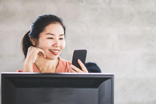 Aziatische bedrijfsvrouw die slimme telefoon met behulp van op het werk