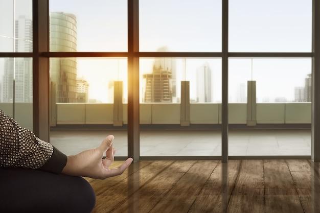 Aziatische bedrijfsvrouw die yoga doet