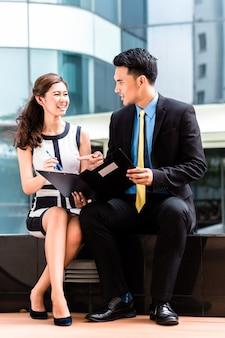 Aziatische bedrijfsvrouw en man die buiten het ondertekenen van contract werken of notities maken