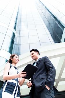 Aziatische bedrijfsvrouw en man die buiten op stootkussen werken