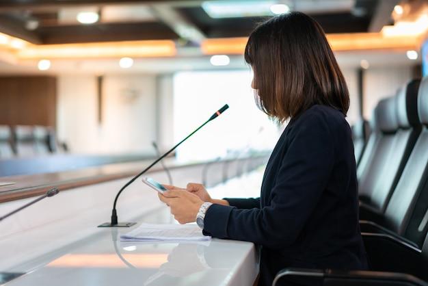 Aziatische bedrijfsvrouw in zwarte de holdingsmicrofoon die van de kostuumhand op het kantoor van de vergaderzaal spreken.