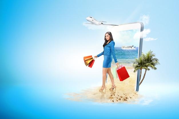 Aziatische bedrijfsvrouw met het winkelen zak op het strand