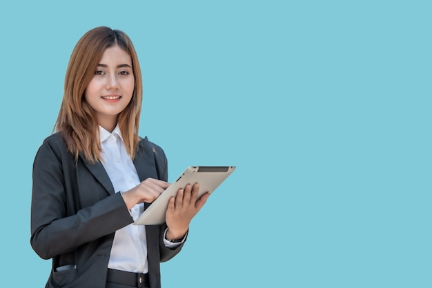 Aziatische bedrijfsvrouw met tabletcomputer die op blauwe banner wordt geïsoleerd