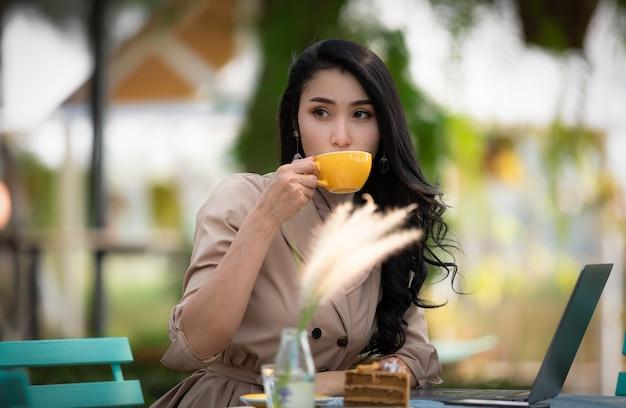 Aziatische bedrijfsvrouwen die koffie en cake drinken is er laptop