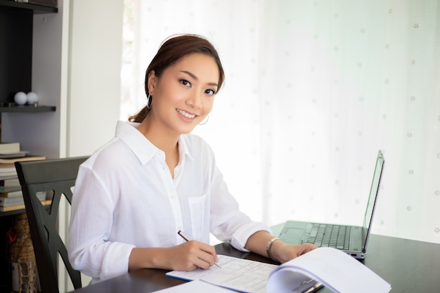 Aziatische bedrijfsvrouwen die notitieboekje gebruiken en gelukkig glimlachen voor het werken