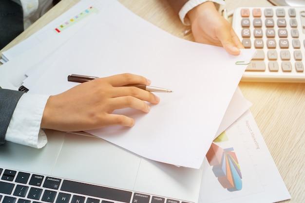 Aziatische bedrijfsvrouwenmanager die aanvrager controleren en ondertekenen die documentenrapporten vult