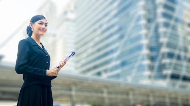 Aziatische bedrijfsvrouwentribunes met zeker het posten en presentatiedocument dossier bij openlucht openbare ruimte