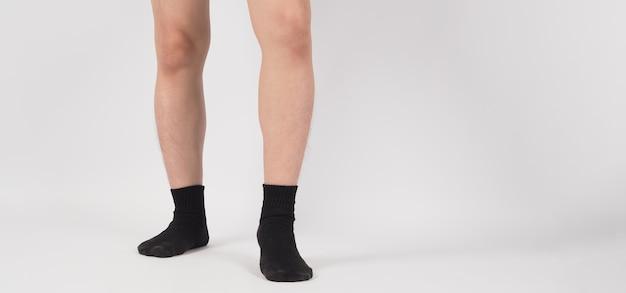 Aziatische been en voet dragen zwarte sok op witte achtergrond. geïsoleerd