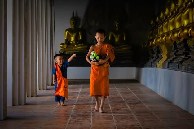 Aziatische beginnende monnik die in tempel phutthaisawan in ayutthaya, thailand lopen.