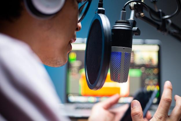 Aziatische beïnvloeders die microfoon gebruiken voor podcasts en geluid opnemen om bestand naar systeem te uploaden. live-opname. online spreken met mobiele. studio-audio-uitzending.