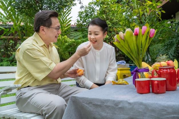 Aziatische bejaarde stellen zorgen voor elkaar door sinaasappels te stropen om te eten. familieconcept, parenconcept
