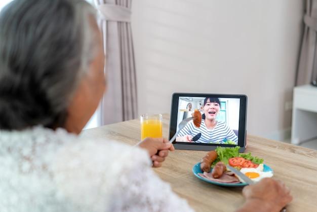 Aziatische bejaarde virtuele happy hour ontmoeting en eten online samen met haar dochter