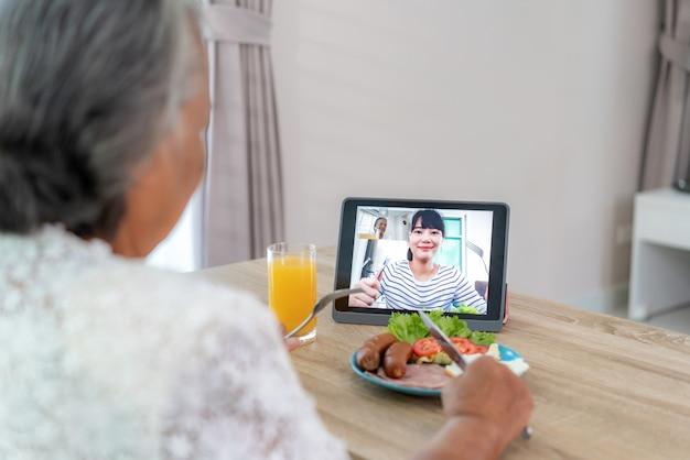 Aziatische bejaarde virtuele happy hour vergadering en het eten van voedsel online samen met haar dochter in videoconferentie met digitale tablet voor een online vergadering in videogesprek