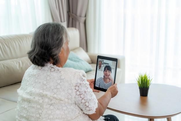 Aziatische bejaarde virtuele happy hour vergadering en online praten samen met haar dochter