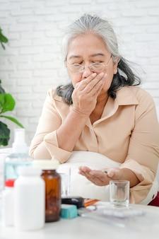 Aziatische bejaarde vrouw blijft thuis om infectie te voorkomen tijdens de coronavirusepidemie ze had koorts en nam medicijnen om het virus te behandelen. thuisisolatie concept, blijf thuis