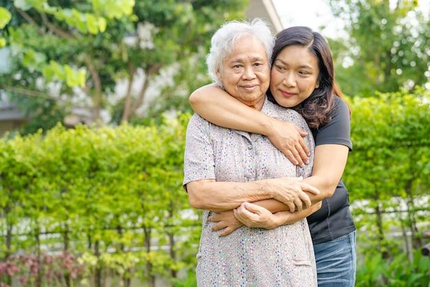 Aziatische bejaarde vrouw met verzorger dochter wandelen en knuffelen met gelukkig in natuurpark.