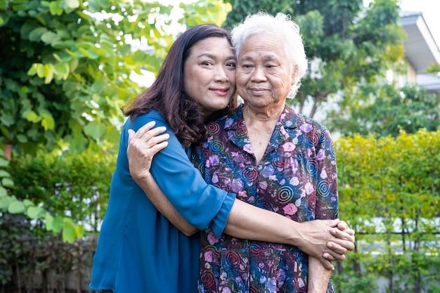 Aziatische bejaarde vrouw met verzorger wandelen met gelukkig in natuurpark.
