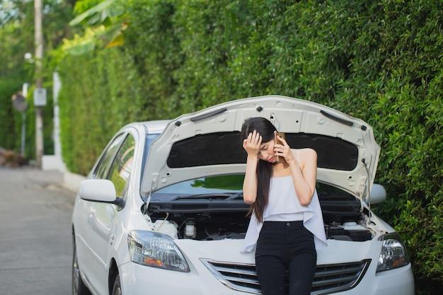 Aziatische beklemtoonde vrouw dichtbij een auto die mobiele telefoon met behulp van