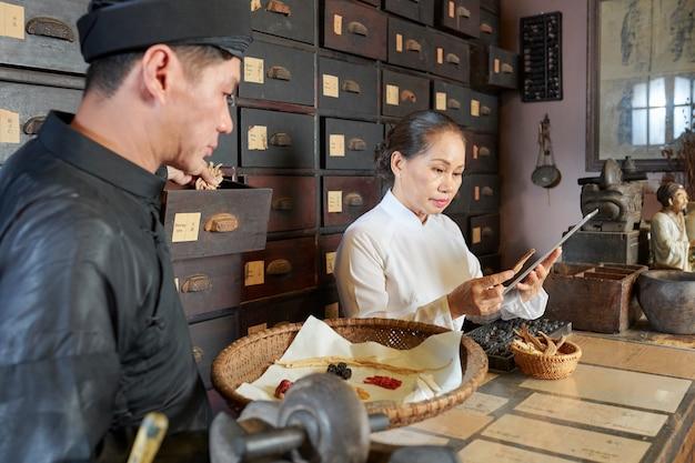 Aziatische beoefenaars werken in oude apotheek