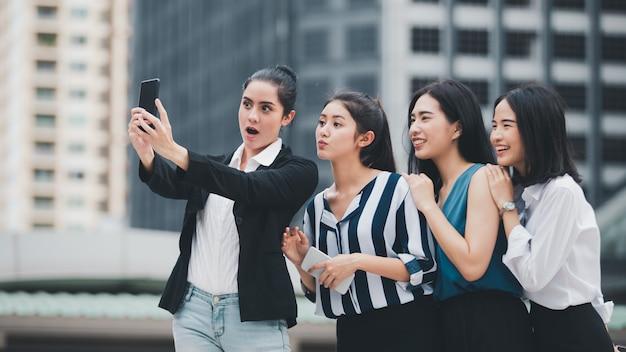 Aziatische beste vrienden die van de levensstijlonderneemster en pret glimlachen hebben die selfie bij de stad lopen