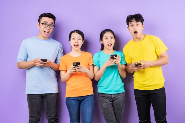 Aziatische beste vriendengroep met behulp van mobiele telefoon op paarse achtergrond
