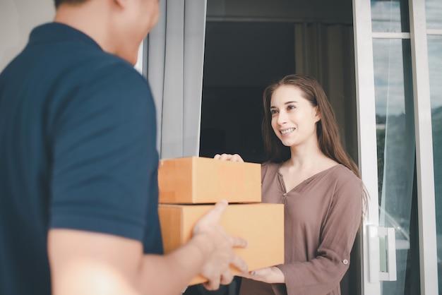 Aziatische bezorgen man in blauwe uniforme verpakkingsdoos