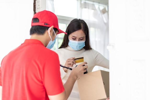 Aziatische bezorger bezorgt koffie en eten aan de klant van de jonge vrouw