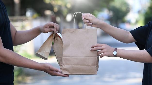 Aziatische bezorger die een papieren zak hanteert met voedsel dat aan de vrouwelijke klant voor het huis wordt gegeven.