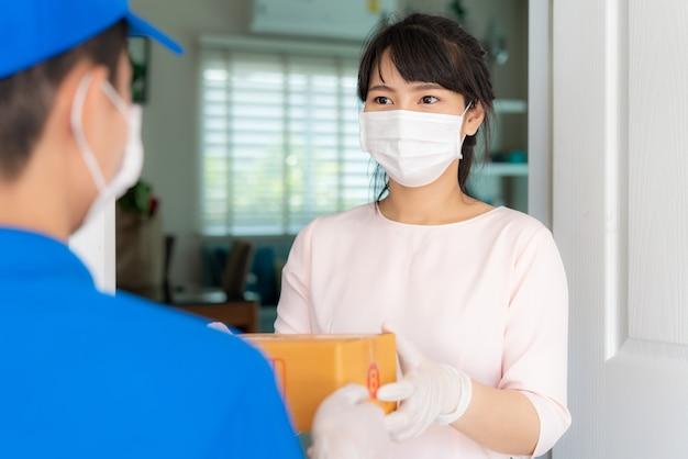 Aziatische bezorger die gezichtsmasker en handschoen in blauw uniform draagt met kartonnen dozen vooraan in huis en vrouw die een levering van dozen van bezorger accepteert tijdens covid-19-uitbraak.