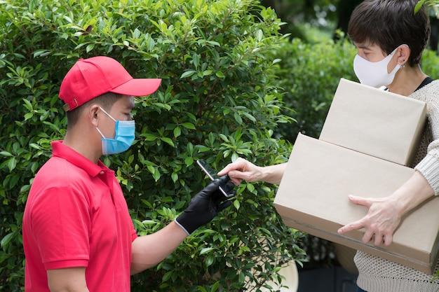 Aziatische bezorger die gezichtsmasker en handschoenen in rood uniform draagt die pakketdoos aan ontvanger levert