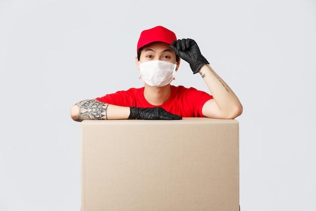 Aziatische bezorger in rode pet en t-shirt, koeriersdienst leunen op kartonnen doos of klantenpakket, saluring als bestelling plaatsen, goederen overbrengen naar mensen die veilig blijven in zelfquarantaine