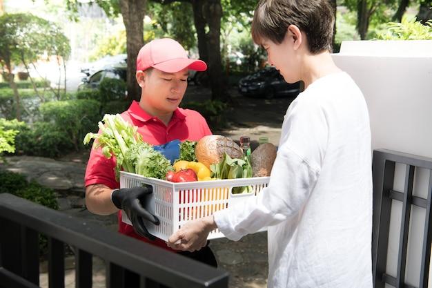Aziatische bezorger in rood uniform die boodschappen doos met voedsel, fruit, groente en drank levert aan de ontvangende vrouw thuis