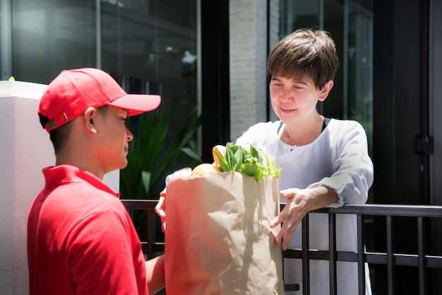 Aziatische bezorger in rood uniform die boodschappenzak met voedsel, fruit, groente en drank levert aan de ontvangende vrouw thuis