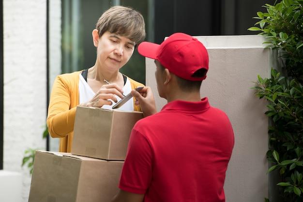 Aziatische bezorger in rood uniform die pakketdoos levert aan de ontvanger van de vrouw thuis met het teken van de ontvanger om het pakket op slim apparaat te ontvangen