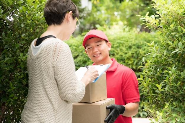 Aziatische bezorger in rood uniform die pakketdoos thuis aflevert bij de ontvanger van de vrouw