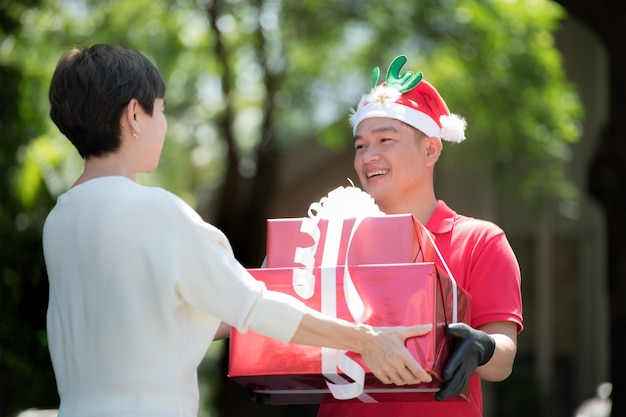 Aziatische bezorger in rood uniform en kerstmuts die cadeau en geschenkdozen levert aan de ontvanger voor het kerstfestival