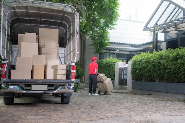 Aziatische bezorger in rood uniform pakketdozen leveren aan de ontvanger van de vrouw thuis