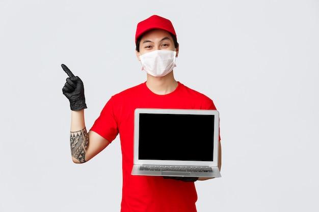 Aziatische bezorger in uniform, rode pet en t-shirt, met beschermend masker en handschoenen om covid 19-verspreiding te voorkomen, bezorgt online bestellingen tijdens zelfquarantaine-isolatie, nodigt bezoekpagina uit