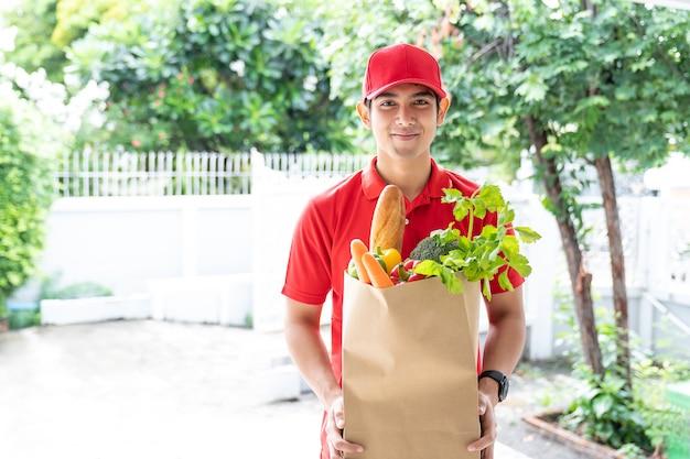 Aziatische bezorger met rode uniform, rode hoed met papieren zak