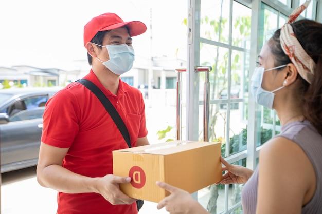 Aziatische bezorgers die een rood uniform dragen met een rode pet en een gezichtsmasker dat kartonnen dozen hanteert