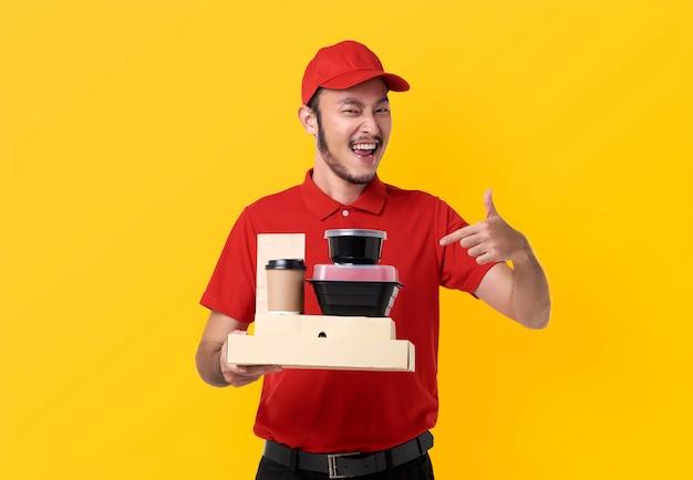 Aziatische bezorgmens die in rood uniform draagt ?? de doos van de holdingslunch en afhaalkoffie die over gele ruimte wordt geïsoleerd