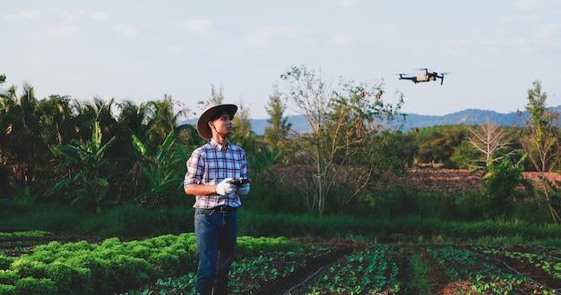 Aziatische boer die slimme drone bestuurt die boven zijn boerderij vliegt