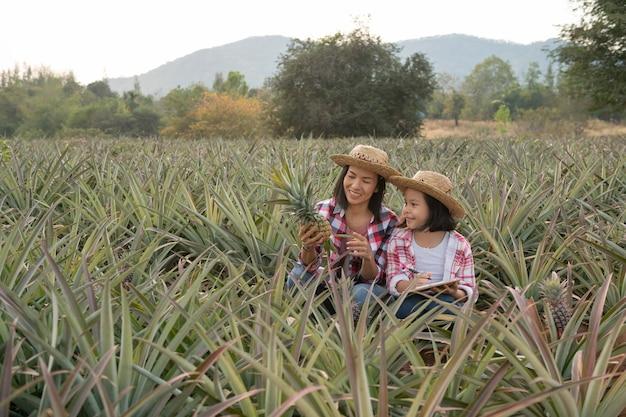 Aziatische boer heeft moeder en dochter die de groei van ananas op de boerderij zien en de gegevens opslaan op de controlelijst van de boer op haar klembord, agricultural industry concept