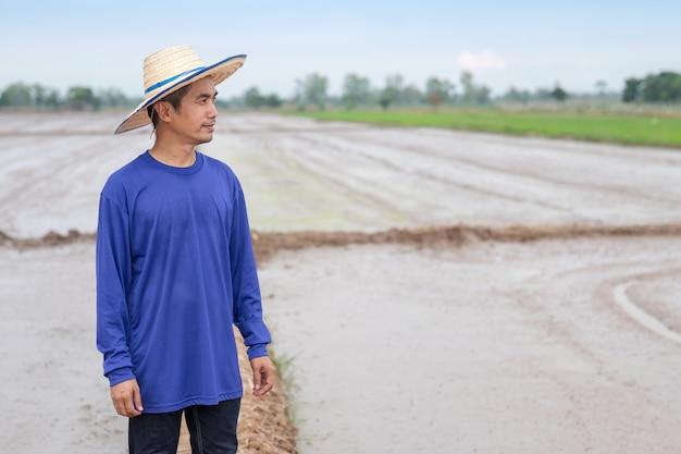 Aziatische boer man draagt een blauw t-shirt en hoed staande rijst kijken naar de boerderij