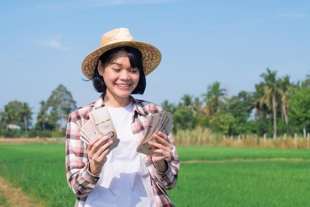 Aziatische boerenvrouw die thais bankbiljetgeld met glimlachgezicht houdt bij groene rijstboerderij