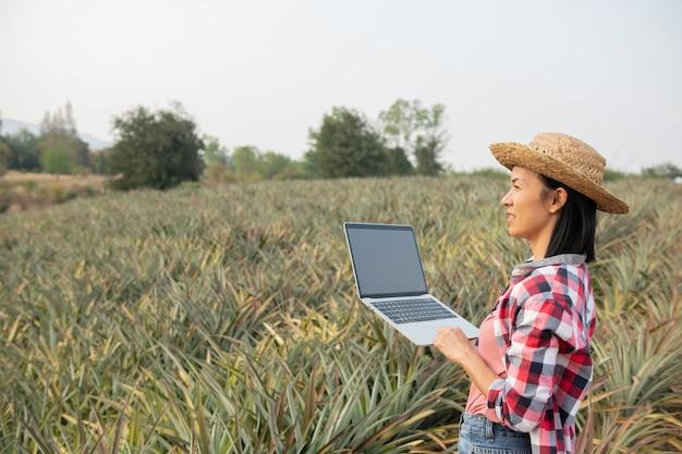 Aziatische boerin ziet de groei van ananas op de boerderij. agrarische industrie, landbouw bedrijfsconcept.