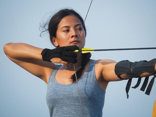 Aziatische boogschietenvrouw die met boog op het strand schieten
