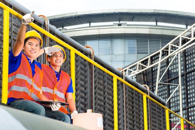 Aziatische bouwer of technici of ingenieurs op technische apparatuur of industriële site