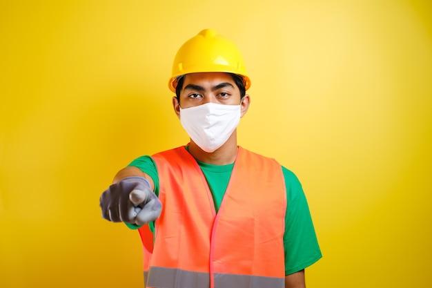Aziatische bouwvakker die een beschermend masker draagt dat naar voren wijst en iemand kiest tegen een gele achtergrond