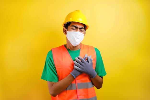 Aziatische bouwvakker die een veiligheidshelm en een beschermend masker draagt, voelt pijn in zijn borst terwijl hij erin knijpt tegen een gele achtergrond